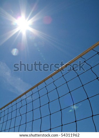 Yellow volleyball net shot from below against blue sky - stock photo