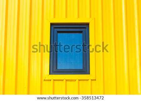 Yellow wall and window from container - stock photo