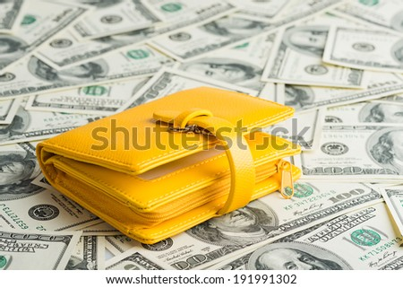 yellow Wallet Resting Upon Many United States One Hundred Dollar Notes.