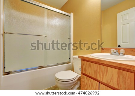 Yellow walls bathroom with glass screened shower bathtub, toilet and wooden vanity cabinet. Northwest, USA