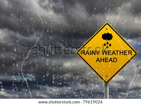 yellow warning sign of bad weather ahead against stormy sky - stock photo