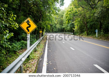 Yellow warning sign winding road with nature - stock photo