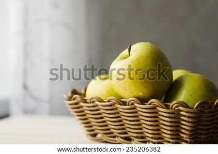 yellow wet fresh apples in a wicker basket - stock photo