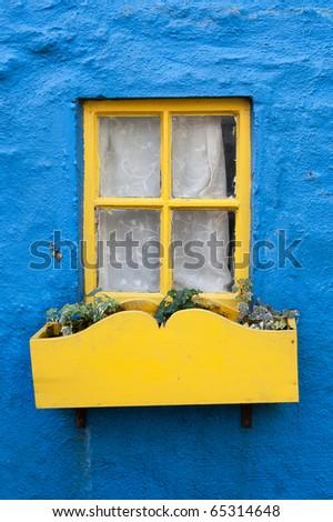 Yellow window on a blue wall. Ireland - stock photo