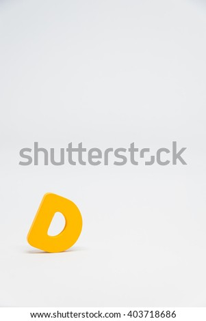 Yellow Wooden alphabet D with white background in Vertical view - stock photo