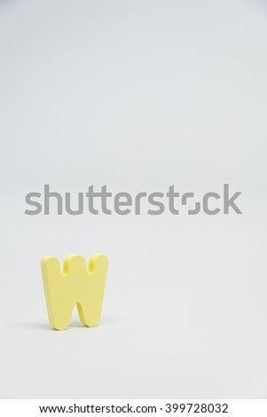 Yellow Wooden alphabet W with white background in Vertical view - stock photo