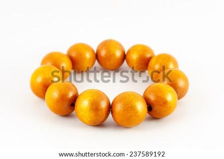Yellow wooden beads bracelet isolated on white - stock photo