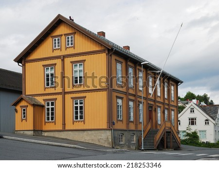 Yellow wooden house is in the modern street of Tromso. Relics of the past is photographed in infrequent sunny day.
