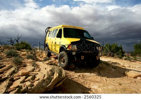 Yellow 4x4 van off road during storm in Utah - stock photo