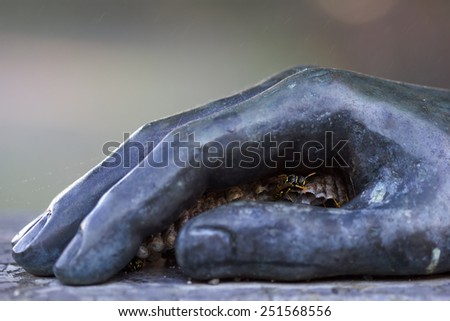 Yellowjacket insect build nest in a bronze hand - symbol of wildlife protecting - stock photo