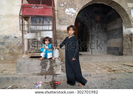 YEMEN, SANAA - MAR 06, 2010: Unidentified girls use drinking water source. Girls grow up in the poorest country with little opportunity for education - stock photo