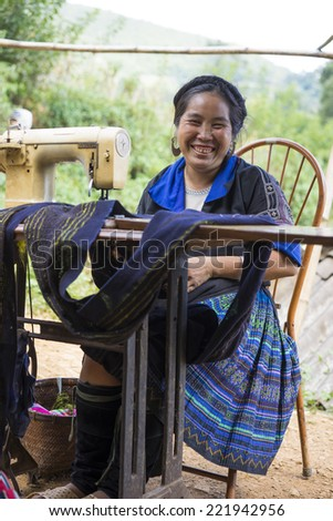 Yen Bai, Vietnam - Sept 27, 2014: Unidentified H'mong woman making clothes by sewing machine nearby her house