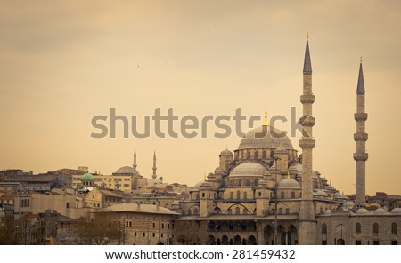 Yeni Cami Mosque or New Mosque in Istanbul at sunset, soft light effect. Panoramic view of the muslim architecture in Turkey capital, district of Sultanahmet in old town. - stock photo
