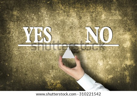 Yes No Balance concept with scale holden by businessman hand against the old background. - stock photo
