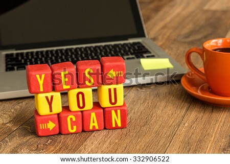 Yes You Can written on a wooden cube in front of a laptop - stock photo