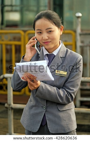 YINXINGTUO, CHINA â?? April 15, 2016: Young Chinese business woman talking on cell phone. Even though Chinese women are contributing to the paid labor force, parity in the workforce has not been reached - stock photo