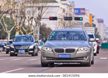 YIWU-CHINA-JANUARY 26, 2016. BMW 5 series on the road. BMW sales will be hit in 2016 by cut-throat competition, slowing Chinese economy and government crackdown on graft and conspicuous consumption. - stock photo