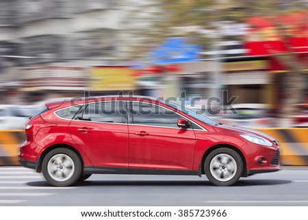 YIWU-CHINA-JANUARY 26, 2016. Red Ford Focus on the road. Ford has set a sales record in China in 2015 as annual sales of Ford vehicles reached 1,115,124, which is up three percent compared to 2014. - stock photo