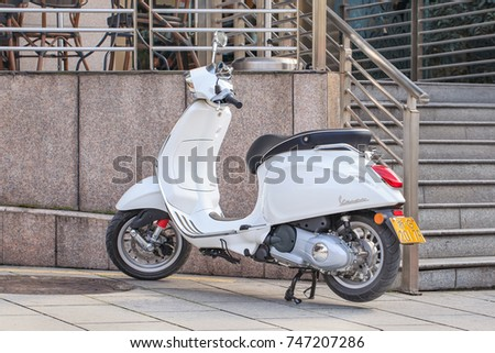 YIWU-JAN. 15, 2016. White Vespa scooter parked in front of a cafe. Vespa is an Italian scooter brand manufactured by Piaggio. Vespa scooters become increasingly popular among youngsters in China.