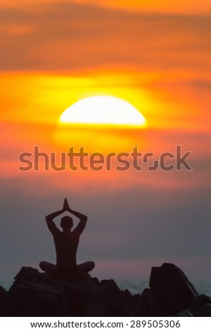 Yoga. A silhouette of the man meditating outdoors at the sunset.  - stock photo