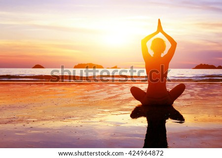yoga and healthy lifestyle background, abstract silhouette of woman meditating on the beach - stock photo