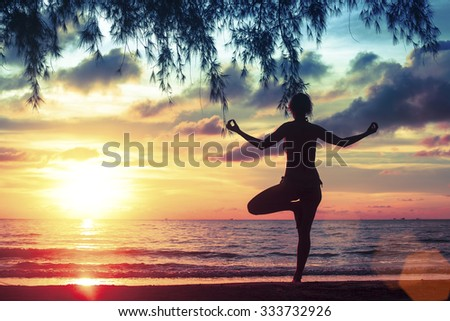 Yoga and healthy lifestyle. Silhouette meditation girl on the background of the sea and sunset.