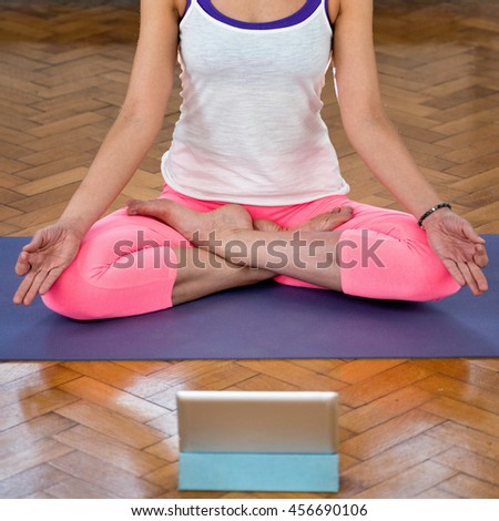Yoga and meditation practiced at home with instructions coming from digital tablet - stock photo