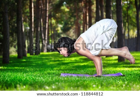 Yoga bakasana crane pose by woman in white costume on green grass in the park around pine trees - stock photo