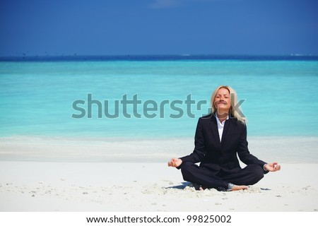 yoga business woman in lotus pose on the beach - stock photo
