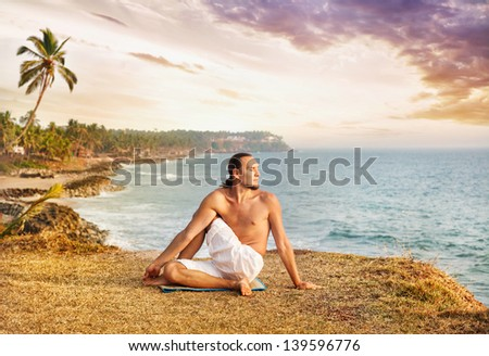 Yoga by man in white trousers on the cliff near the ocean in Kerala, India - stock photo