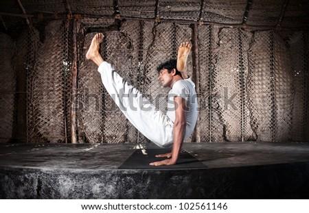 Yoga chakorasana pose by Indian man in white cloth in yoga shala, Varkala, Kerala, India - stock photo