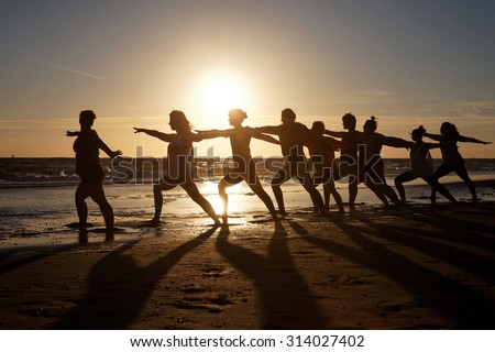 yoga class as silhouette at sunset by the sea - stock photo