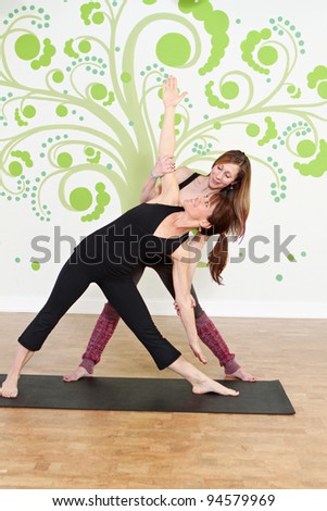 Yoga Class instructor with student - stock photo