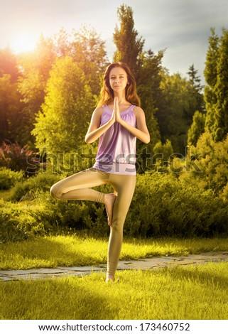 Yoga exercising (Vrikshasana) - stock photo