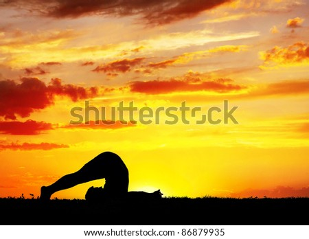 Yoga Halasana plough inverse pose by Man in silhouette with orange sunset sky background. Free space for text - stock photo