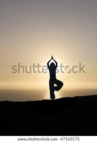 yoga in front of beautiful sunset - stock photo