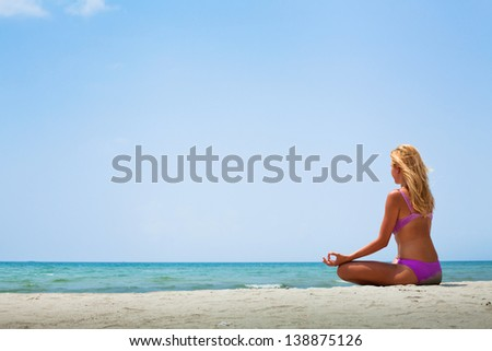 yoga in sunny day on the beach - stock photo