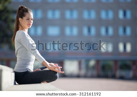 Yoga in the city: beautiful young fit woman meditating, breathing, sitting in Half Lotus Posture in front of building on the street on summer day, Ardha Padmasana, copy space - stock photo