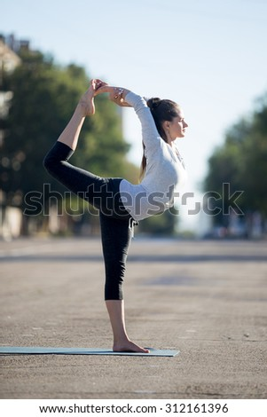 Yoga in the city: beautiful young sporty woman wearing sportswear working out on the street on summer day, doing Natarajasana, Dancing Shiva pose, full length, side view - stock photo