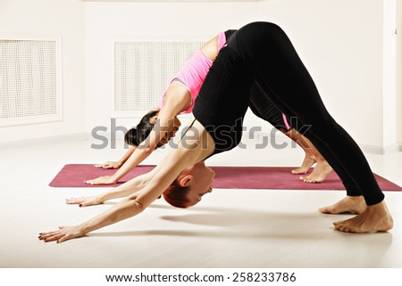 Yoga instructor shows downward facing dog pose to student - stock photo
