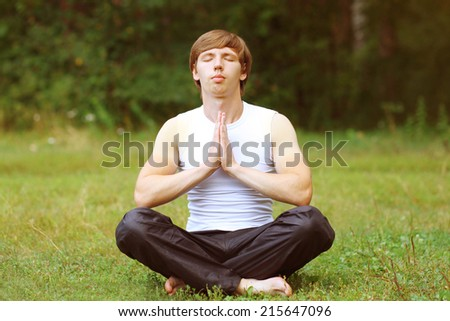 Yoga man relaxation on the grass  - stock photo