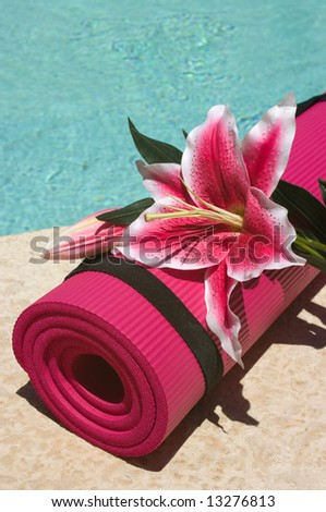 Yoga mat and a beautiful lily near a pool - stock photo