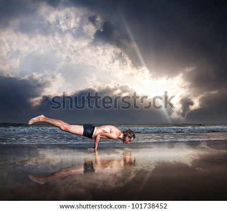 Yoga Mayurasana peacock handstand balancing pose by fit man on the beach near the ocean at dramatic sunset sky - stock photo