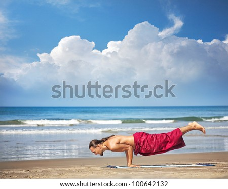 Yoga Mayurasana peacock handstand balancing pose by man with long hair in red trousers on the beach at ocean background - stock photo