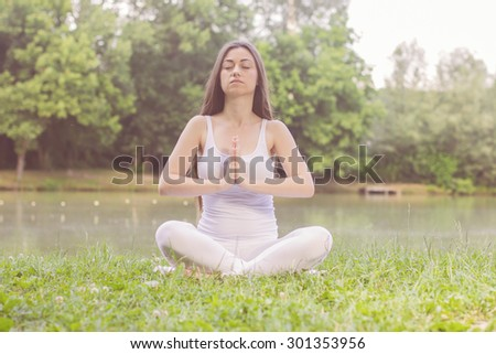 Yoga Meditating Relax Young Woman Outdoor. Healthy Lifestyle at beautiful summer day in nature. - stock photo