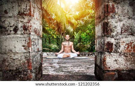 Yoga meditation by man with beard in white trousers on the roof at palms and sunset sky background in India - stock photo