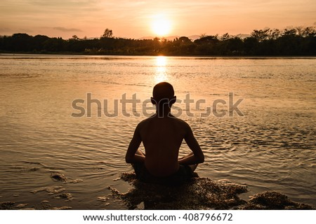 Yoga meditation in river during the sunset, Thailand