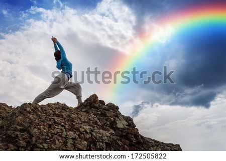 Yoga meditation on mountain top. Rainbow in background. - stock photo