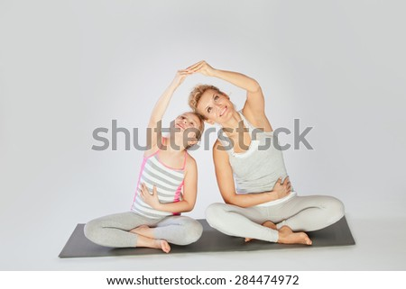 Yoga / Mother and daughter doing yoga exercise - stock photo