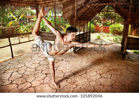 Yoga natarajasana dancer pose by fit man in white trousers on the drought earth in yoga shala, Varkala, Kerala, India - stock photo